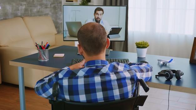 Instructions du médecin lors d'un appel vidéo pour un homme handicapé en fauteuil roulant.