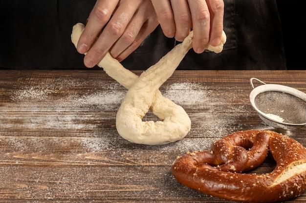 Instructions étape par étape pour faire des bretzels. le cuisinier étale la pâte et étale le bretzel