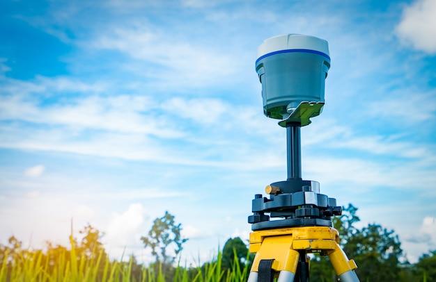 Instrument d'arpentage gps sur ciel bleu, nuages cumulus et champ de riz
