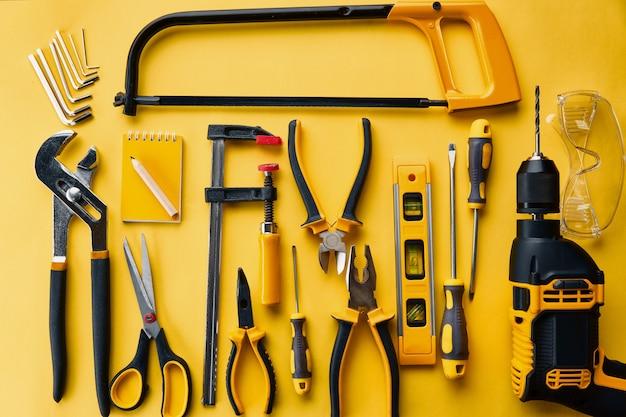 Instrument d'atelier professionnel, vue de dessus. outils de menuisier, équipement de construction, tournevis et pieux, scie à métaux et niveau, ciseaux et perceuse