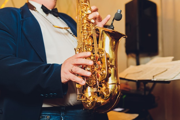 Instrument de musique classique saxophone saxophoniste avec gros plan sax alto sur fond noir.