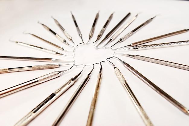 Instruments dentaires en forme de coeur sur fond blanc