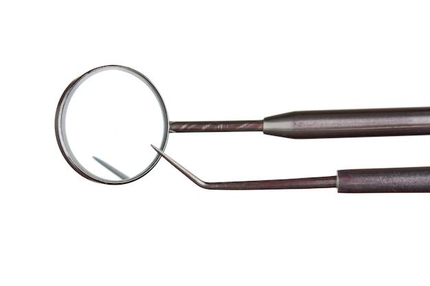 Instruments dentaires isolés sur une surface blanche