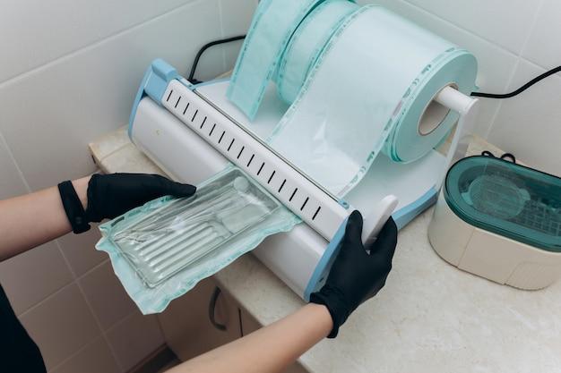 Les instruments dentaires scellés stériles sont empilés dans un tiroir. gros plan des mains avec des gants dans les endroits autoclave médical pour stériliser les instruments chirurgicaux et dentaires.