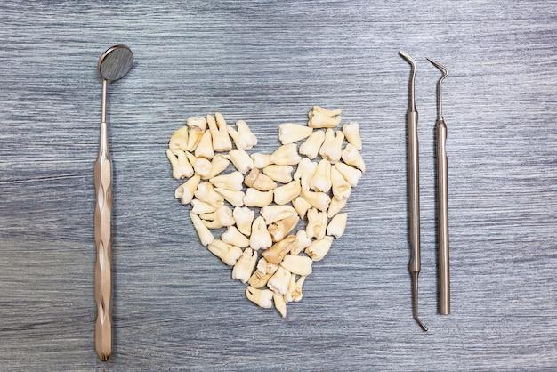 Les instruments du dentiste et les dents des gens reposent sur la table disposée en forme de cœur. outils pour les dentistes et les dents des personnes
