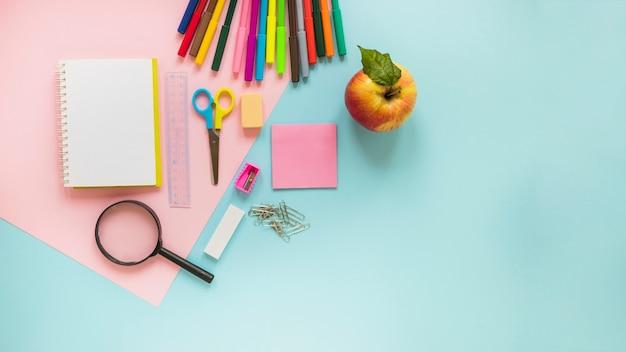 Instruments d'écriture et pomme posés