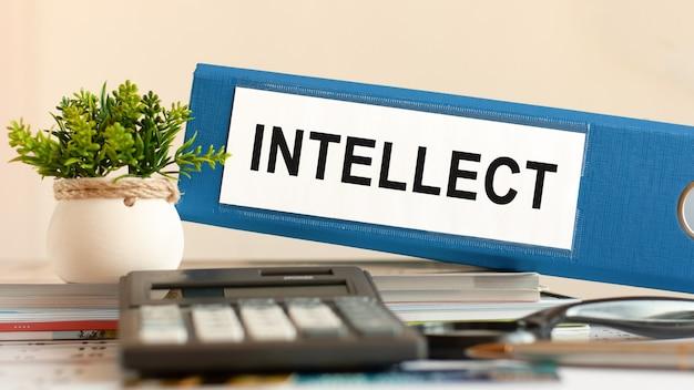 Intellect - classeur bleu sur le bureau au bureau avec calculatrice, stylo et plante verte en pot. peut être utilisé pour les affaires, la finance, l'éducation, l'audit et le concept fiscal. mise au point sélective.