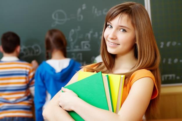 Intelligente fille tenant des livres dans la salle de classe