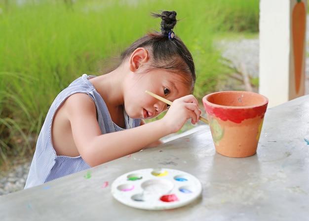 Intend enfant asiatique fille peinture sur plat en terre cuite.