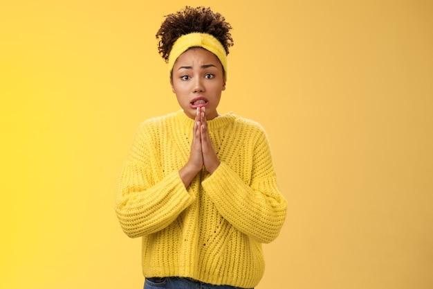 Intense inquiète perplexe jeune femme afro-américaine sombre se tenir la main prier froncer les sourcils rampant mendier faveur debout troublée mauvaise situation besoin d'aide pardon se sentir maladroit, fond jaune.