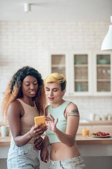 Intéressant ici. femme jeune couple adulte debout à la recherche avec intérêt au smartphone dans la cuisine à la lumière du jour