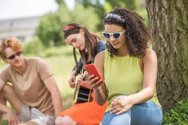 Intéressant ici. fille souriante bouclée regardant dans la petite amie du smartphone avec guitare et petit ami assis à distance sur un pique-nique dans le parc