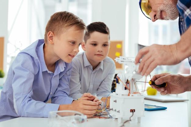 Intéressante leçon. de beaux garçons intelligents assis au bureau tout en regardant leur professeur