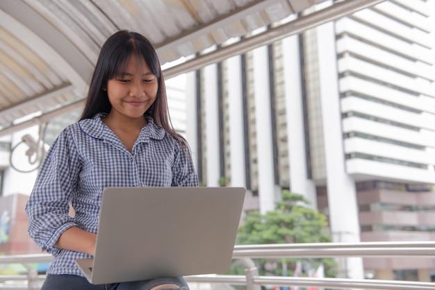 Intéressantes filles asiatiques tapant, discutant, assis, discutant, répondant à l'aide d'un ordinateur portable