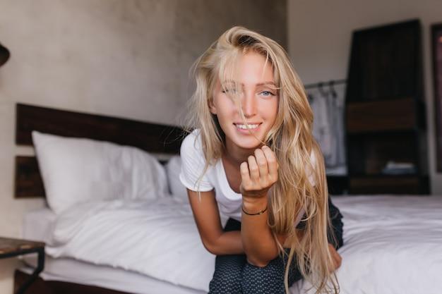 Intéressé femme blanche aux cheveux longs à la recherche de la caméra. sensuelle femme détendue se détendre à la maison.