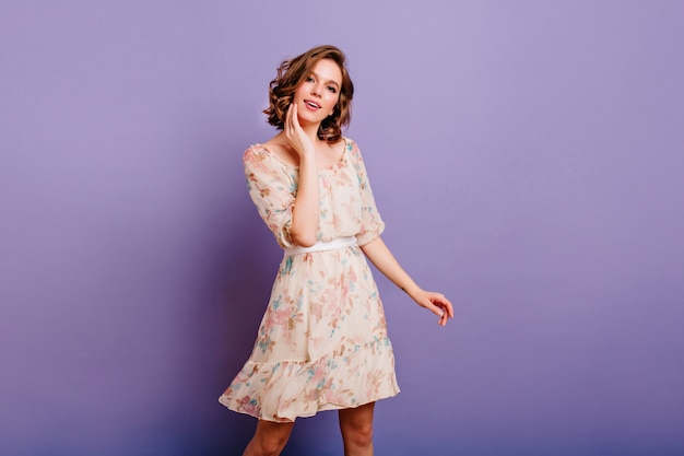 Intéressé jeune femme en jolie robe touchant doucement son visage sur fond violet