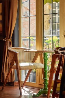 Intérêt cosy, un fauteuil et une table ronde avec une tige verte près de la grande fenêtre