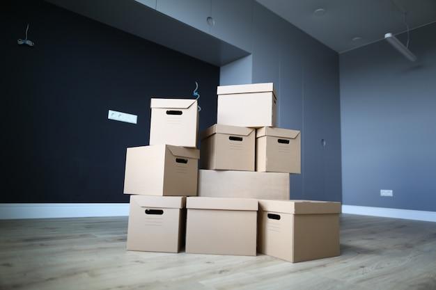 Intérieur d'un appartement vide, au centre se trouvent des boîtes