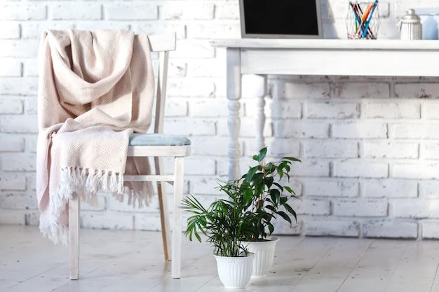 Intérieur blanc avec chaise, tapis et petite table