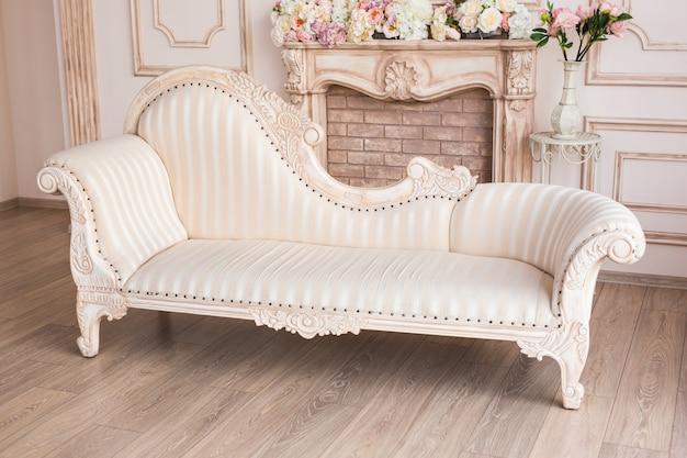 Intérieur blanc classique du salon avec canapé et fauteuil près de la cheminée.