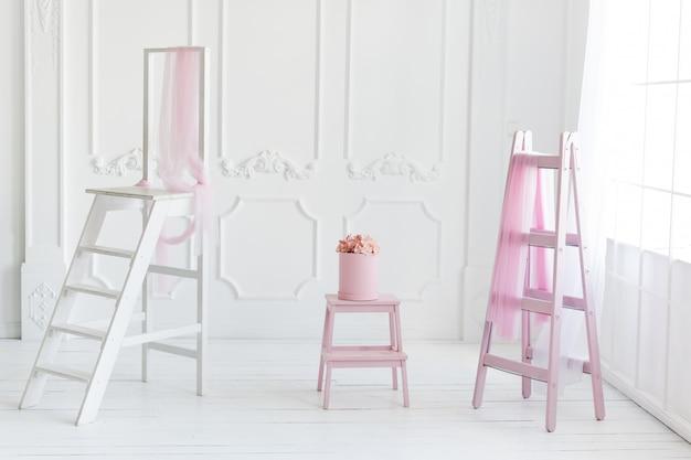 Intérieur blanc simple, décor d'échelle rose et fleurs dans la boîte.