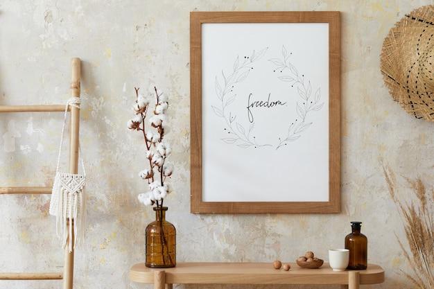 Intérieur boho beige du salon avec cadre, accessoires élégants, fleurs séchées dans un vase, console en bois et hutte en rotin suspendue dans une décoration élégante.