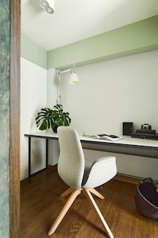 Intérieur de bureau à domicile élégant dans un appartement moderne avec bureau, fauteuil et autres accessoires de bureau et personnels. espace ensoleillé avec murs blancs et menthe. des détails. modèle