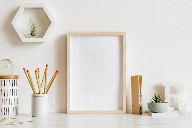 Intérieur de bureau à domicile scandinave avec cadre d'affiche en bois, accessoires de bureau de conception, rubans, fournitures, notes, mémo, plantes aériennes. concept minimaliste. modèle.