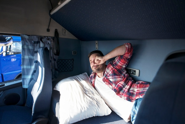 Intérieur de la cabine du camion avec chauffeur dormant dans son lit