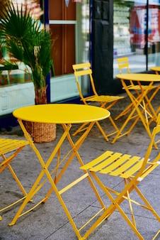 Intérieur de café de rue avec table et chaises jaunes