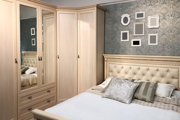 Intérieur de chambre classique avec des meubles en bois naturel et un lit double confortable avec des coussins et des cadres photo sur le mur