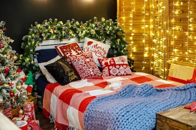 Intérieur de la chambre à coucher dans une décoration sombre décorée pour noël. le lit avec des draps bleu foncé et de nombreux oreillers est recouvert d'une couverture en laine en fil de mouton hyper large