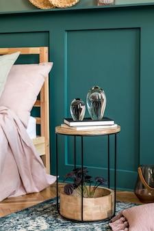 Intérieur de chambre élégant avec table basse design, plante, sculpture, étagère et accessoires personnels élégants. beaux draps, couverture et oreiller. home staging moderne. lambris mural.