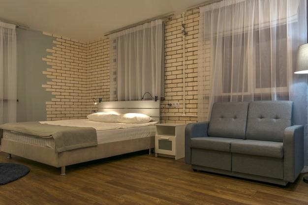 Intérieur de la chambre, lit double, canapé et grandes fenêtres.
