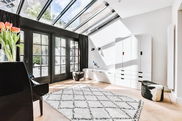 Intérieur de la chambre moderne éclairée par la lumière du soleil de la fenêtre du plafond et de la porte dans la maison moderne