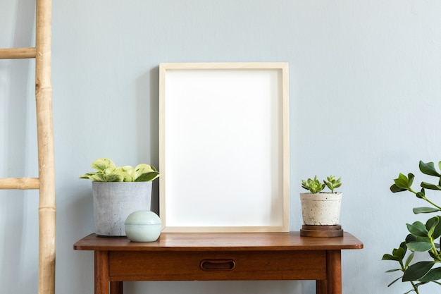Intérieur de la chambre scandinave avec cadre photo sur l'étagère en bambou marron avec de belles plantes dans différents pots hipster et design