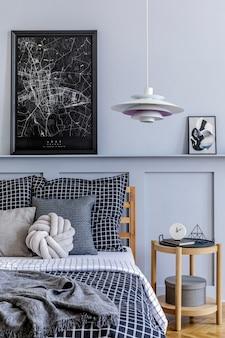 Intérieur de chambre scandinave élégant avec table basse design, cadres, livre, horloge, décoration, accessoires personnels, beaux draps, couverture et oreillers.
