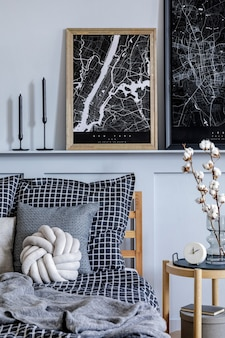 Intérieur de chambre scandinave élégant avec table basse design, plante, cadres, livre, horloge et décoration