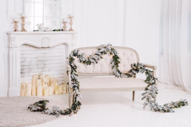 Intérieur classique blanc avec cheminée, canapé et décorations de noël.