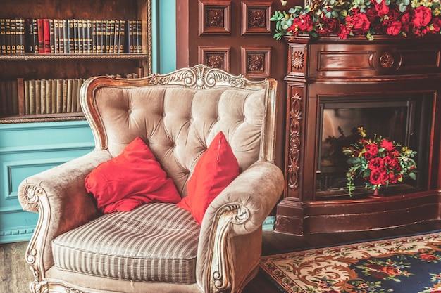 Intérieur classique de luxe de la bibliothèque à domicile. salon avec bibliothèque, livres, fauteuil, canapé et cheminée
