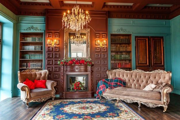 Intérieur classique de luxe de la bibliothèque à domicile. salon avec étagère, livres, fauteuil, canapé et cheminée.