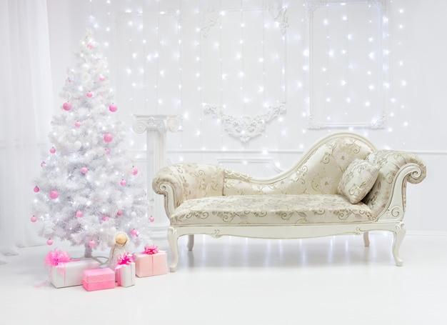 Intérieur classique de noël dans des tons blancs et roses avec un canapé