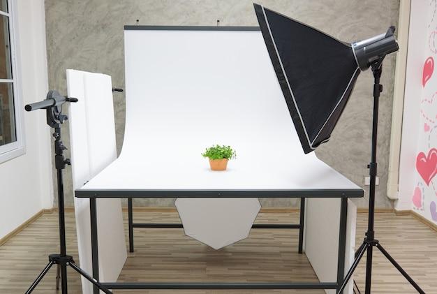 Intérieur avec climatiseur studio blanc table de scène de séance photo et partition avec équipement de photographe professionnel softbox réflecteur flash stroboscopique sur trépied prêt pour les produits de prise de vue.