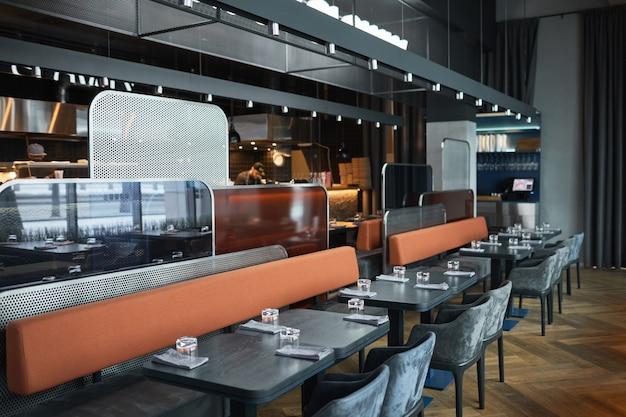 Intérieur contemporain du bistro café de couleur noire avec de longs canapés séparés par des panneaux métalliques et en verre
