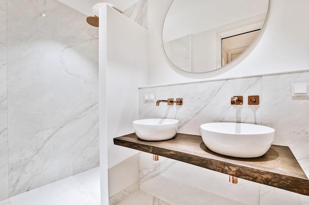 Intérieur contemporain de salle de bain avec douche et toilettes près de lavabos en céramique blanche à plat
