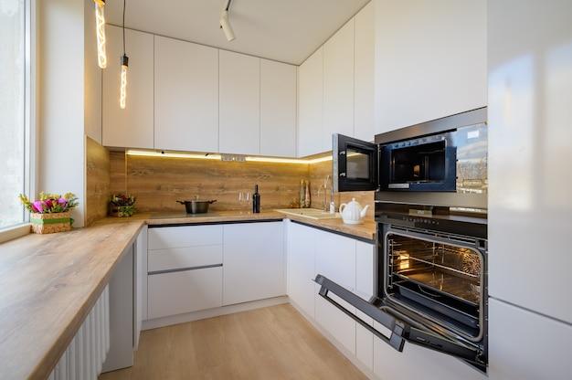 Intérieur de cuisine en bois blanc et beige moderne avec four ouvert