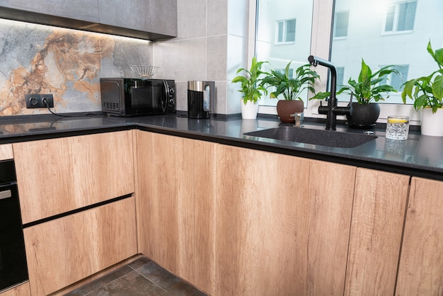 Intérieur d'une cuisine équipée moderne avec décor en pierre et armoires en bois avec appareils électriques dans un appartement de ville dans un immeuble de grande hauteur