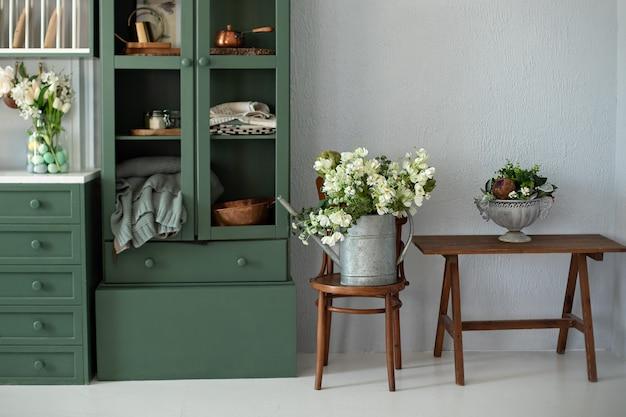 Intérieur de cuisine avec mobilier beau bouquet de fleurs en arrosoir sur chaise en bois par placard cuisine avec fleurs en vase