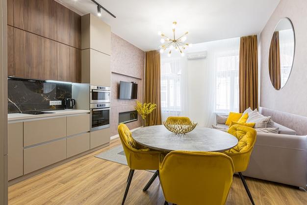 Intérieur d'une cuisine moderne et élégante dans des couleurs pastel, gris, avec un insert de marbre noir