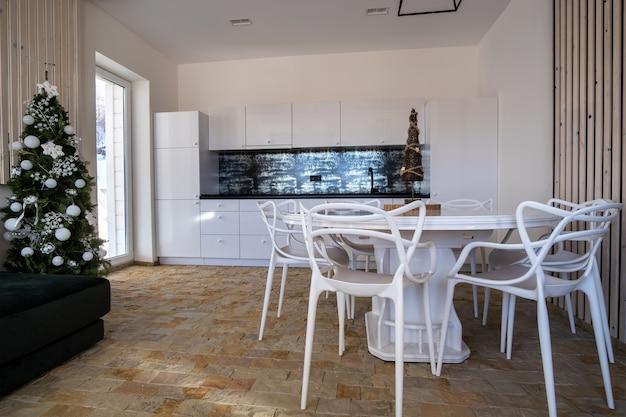 Intérieur d'une cuisine moderne et spacieuse aux murs blancs, éléments décoratifs en bois, mobilier contemporain et grand canapé moelleux.